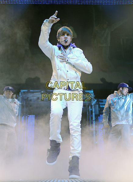 "JUSTIN BIEBER.performs live during his ""My World Tour""  at Honda Center in Anaheim, California, USA, October 27th 2010..concert gig on stage music full length white jacket purple hoodie jeans trainers hi-tops  dry ice steam smoke    hand arm dancing one foot leg    jumping raised up                                                           .CAP/RKE/DVS.©DVS/RockinExposures/Capital Pictures."