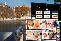Market stall displaying artwork for sale on the banks of the Seine, Paris, France.