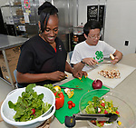 4-H ambassador Caleb Kinzinger, 16, from Freeburg, Ill and Jackie Joyner Kersee chat as they slice fresh-picked vegetables and chicken for a salad inside the JJK Center on Thursday, May 30, 2019 in East St. Louis, Ill. (Tim Vizer/AP Images for National 4-H Council)