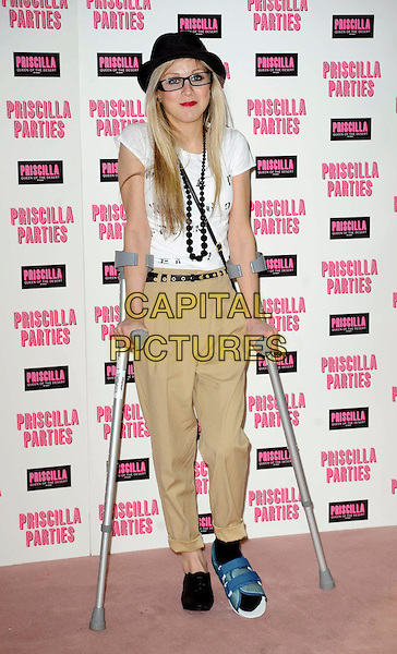 NIKKI GRAHAME.The launch of 'Priscilla Parties' at the Palace Theatre, London, England, UK, January 24th 2011.full length white top t-shirt black hat glasses belt beige trousers crutches beads necklace foot injury injured chinos .CAP/DS.©Dudley Smith/Capital Pictures