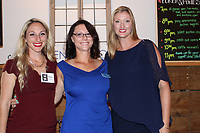 NWA Democrat-Gazette/CARIN SCHOPPMEYER Kelsey Griffing (from left), Krissi Long and Megan Smits welcome Horses for Healing supporters to Poker & Ponies.