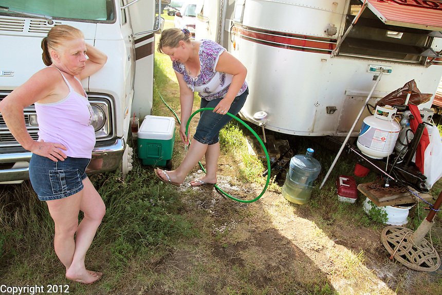 Jean, left, and Ruby talk behind Ruy's trailer. Jean Tasby, 53, most recently from Coeur d'Alene, Idaho, is originally from Longview, Washington. Ruby Tieu, 42, is from Bremerton, Washington. Both came to Williston, ND with their husbands to find work. All found work at jobs they are happy with. Most residents of the field did not have access to the hose, but since Ruby and Jean checked in on Dale, he let them use the water.