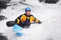 Heather Armitage paddles through a hole in a whitewater kayak on the Kananaskis River, Kananaskis County, Alberta, Canada