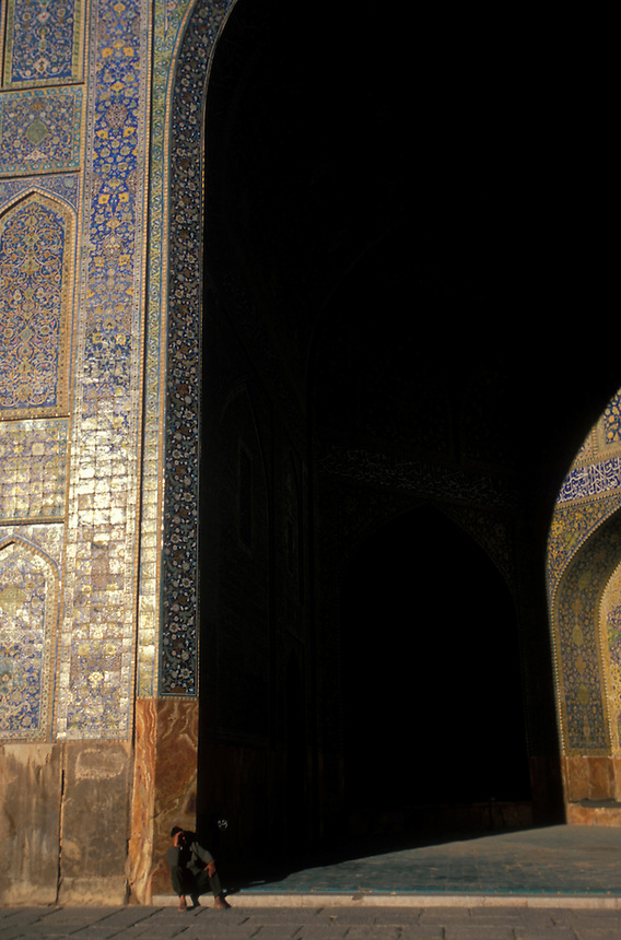 An Iranian man is dwarfed by the main archway of the Emam Mosque, Esfahan, Iran, 2006. Photo: Ed Giles.