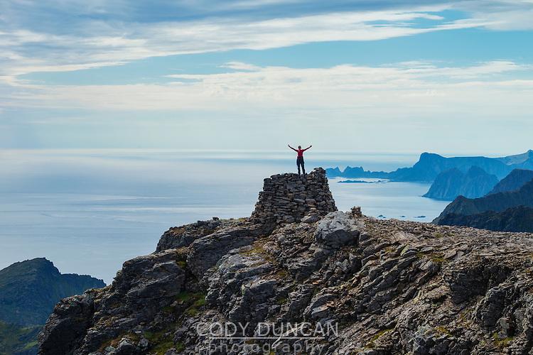 Female hiker stands on summit cairn of Støvla mountain peak, Moskenesøy, Lofoten Islands, Norway
