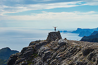 Female hiker stands on summit cairn of Støvla mountain peak, Moskenesøy, Lofoten Islands, Norway