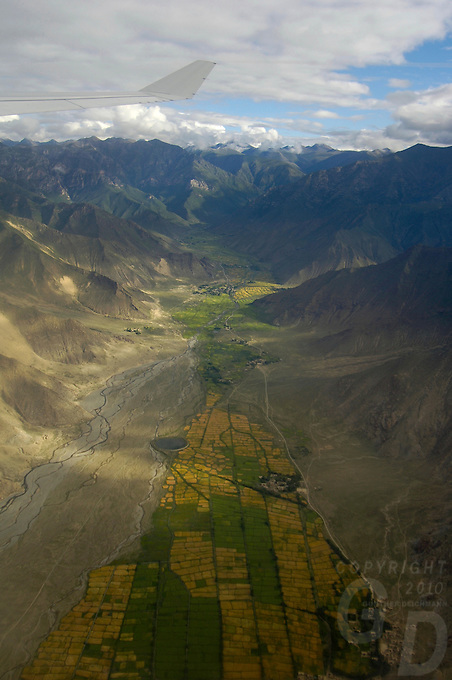 Aerial on the approch to Lhasa Tibet, view from a commercial.airliner, approximate 15 minutes before Lhasa,in the foreground farm, land.