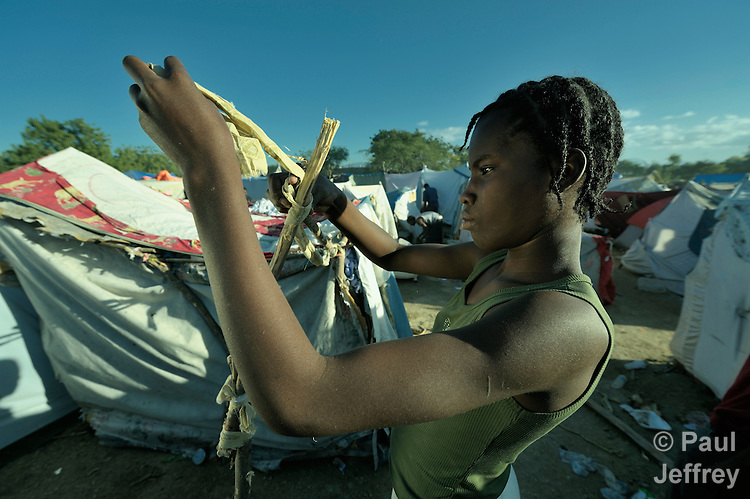 A girl helps build a shelter in a camp for homeless families set up on a golf course in Port-au-Prince, Haiti, which was ravaged by a January 12 earthquake.