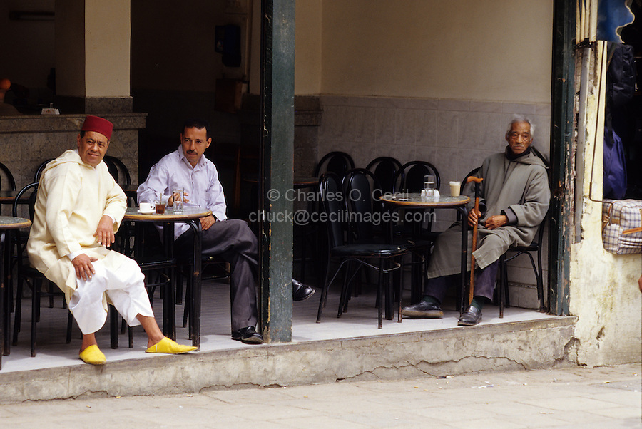 Fez, Morocco - Coffee Shop in the Old City.  The customers show that both western-style and traditional Moroccan style clothes and shoes are worn by men.