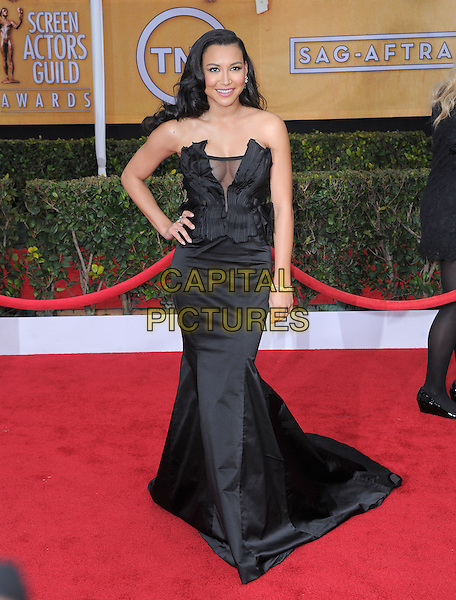 Naya Rivera (wearing Donna Karan).Arrivals at the 19th Annual Screen Actors Guild Awards at the Shrine Auditorium in Los Angeles, California, USA..27th January 2013.SAG SAGs full length black strapless dress satin silk corseted corset gown sheer accordion pleating decolletage hand on hip cleavage .CAP/DVS.©DVS/Capital Pictures.
