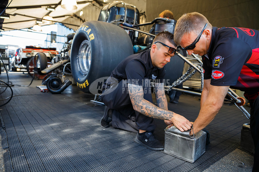 Jul 23, 2017; Morrison, CO, USA; NHRA funny car driver Jonnie Lindberg packs his parachutes with the help of a crew member during the Mile High Nationals at Bandimere Speedway. Mandatory Credit: Mark J. Rebilas-USA TODAY Sports