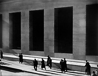 New York City, 1915 : Aerial view of pedestrians walking along Wall Street in strong sunlight and building in background with large recesses. Photograph by Paul Strand