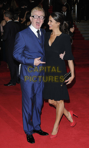 Chris Evans & Natasha Shishmanian.Royal World Premiere of 'Skyfall' held at the Royal Albert Hall, London, England..October 23rd, 2012.full length blue suit glasses black dress clutch bag married husband wife profile mouth open hand arm funny .CAP/CAN.©Can Nguyen/Capital Pictures.