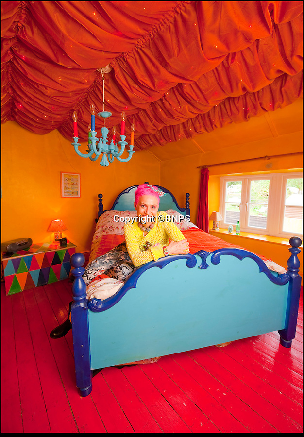 BNPS.co.uk (01202 558833)<br /> Pic: PhilYeomans/BNPS<br /> <br /> Artist Mary Rose Young in one of the bedroom's.<br /> <br /> Britain's wackiest property has come on the market...And the estate agents mantra of paint everything magnolia has definately not been applied.<br /> <br /> It may look like an idyllic cottage in the Forest of Dean from the outside but ceramic artist Mary Rose Young's unique taste has transformed the interior into what looks like something from Alice in Wonderland.<br /> <br /> The three-bedroomed house is decorated from head to toe in crazy colours, clashing patterns, and enormous murals,<br /> each room is covered in the garish designs, including the bathroom, where even the sink and toilet have been adorned in bright tiles.<br /> <br /> Estate agents Bidmead Cook now have the tricky task of showing prospective punters round the £500,000 property.
