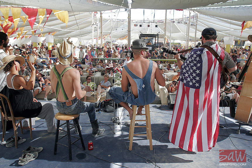 """BLACK ROCK CITY, NV - AUGUST 27,2008:  The theme for Burning Man in 2008 is """" The American Dream"""", dressed appropriately, for their performance at center camp, bluegrass group; Jacob Groupman and the little bitches perform, August 27,2008. Participants from around the world are converging in Nevada for the annual art event which attracts over 30,000 people annually."""