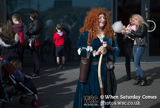 Morecambe 0 Plymouth Argyle 2, 25/03/2016. Globe Arena, League 2. A woman dressed as Merida from Brave entertaining children outside the Globe Arena before Morecambe hosted Plymouth Argyle in a League 2 fixture. The stadium was opened in 2010 and replaced Morecambe's traditional home of Christie Park which had been their home since 1921, the year after their foundation. Plymouth won this fixture by 2-0 watched by 2,081 spectators, in a game delayed by 30 minutes due to traffic congestion affecting travelling Argyle fans.  Photo by Colin McPherson.