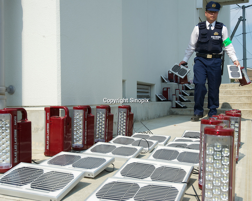 A police man arranges solar cells to charge batteries for flashlights at an evacuation shelter in  Minamisanriku, Myiagi, Japan.The fishing port of Minamisanriku, Miyagi, Japan where the popultion was reduced from 18,000 to about 8,000 when 10,0000 where washed out to sea.<br /> <br /> Photo by Richard Jones/ Sinopix