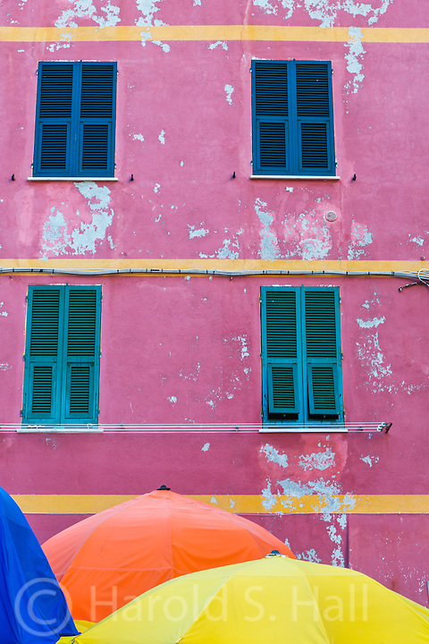 Brightly colored umbrellas add to the color of one of the five fishing villages, Vernazza in Cinque Terra, Italy.