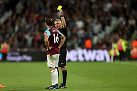 Mark Noble of West Ham United is shown a yellow card by referee Jonathan Moss during West Ham United vs Manchester United, Premier League Football at The London Stadium on 10th May 2018