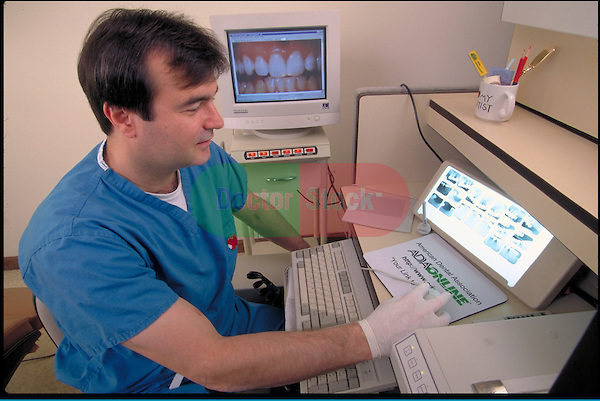 dentist viewing x-rays of teeth while working with computer