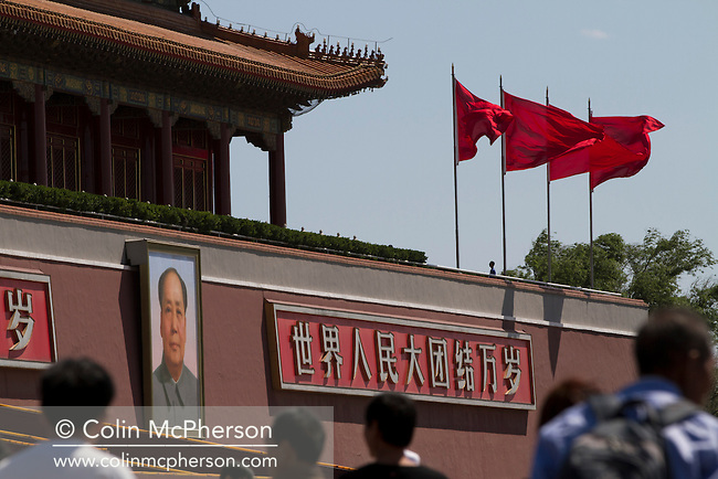 People passing next to a portrait of Chairman Mao and red flags fluttering on the Rostrum in Tiananmen Square, Beijing, China. Tiananmen Square is a large city square in the center of Beijing, China, named after the Tiananmen Gate (Gate of Heavenly Peace) located to its North, separating it from the Forbidden City. Tiananmen Square was the third largest city square in the world and is visited by tens of thousands of foreign and Chinese tourists each year.