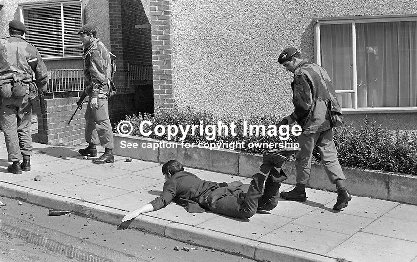 British soldier stands guard with a rifle over a young rioter in the Lenadoon Avenue area, of Belfast, N Ireland, during widespread disturbances which followed the introduction of internment without trial. 387/71, 197108000387a...Copyright Image from Victor Patterson, 54 Dorchester Park, Belfast, UK, BT9 6RJ..Tel: +44 28 9066 1296.Mob: +44 7802 353836.Voicemail +44 20 8816 7153.Skype: victorpattersonbelfast.Email: victorpatterson@mac.com.Email: victorpatterson@ireland.com (back-up)..IMPORTANT: If you wish to use this image or any other of my images please go to www.victorpatterson.com and click on the Terms & Conditions. Then contact me by email or phone with the reference number(s) of the image(s) concerned.