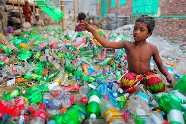 A young boy sorts through piles of plastic drinks bottles collected from Dhaka's streets in a factory producing PET (Polyethylene terephthalate) flakes. Bangladesh exports over 20,000 tonnes of PET flakes made in 3,000 factories located across the country in an industry worth GBP 7 million in 2010. The business is growing by 20 percent every year.