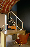 A simple concrete desk and banquette sofa are integrated into the design of this open staircase