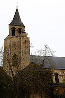 The bell tower of the church of Saint Germain in Paris, under a cloudy sky, with a bare tree. Digitally Improved Photo.