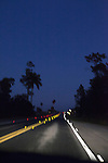 Road lit by headlights while driving at night through Everglades National Park, Florida, USA