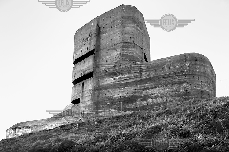 A German bunker used by the German Army during its occupation of the Channel Islands in WWII is visible on a hill in Guernsey. The Atlantic Wall (or Atlantikwall in German) was a system of defensive structures built by Nazi Germany between 1942 and 1945, stretching over 1,670 miles (2,690 km) along the coast from the North of Norway to the border between France and Spain at the Pyrenees. The wall was intended to repulse an Allied attack on Nazi-occupied Europe and the largest concentration of structures was along the French coast since an invasion from Great Britain was assumed to be most likely. Slave labour and locals paid a minimum wage were drafted in to supply much of the labour. There are still thousands of ruined structures along the Atlantic coast in all countries where the wall stood except for Germany, where the bunkers were completely dismantled.