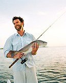 USA, Florida, fisherman holding fishing rod and Redfish, smiling, New Smyrna Beach
