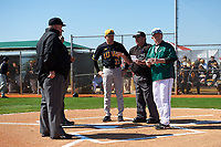 Dartmouth Big Green head coach Bob Whalen (right) during the lineup exchange with Rick Heller (21) and umpires Dan Deim (center), Dorsey Hager, and Kyle Reese before a game against the Iowa Hawkeyes on February 27, 2016 at South Charlotte Regional Park in Punta Gorda, Florida.  Iowa defeated Dartmouth 4-1.  (Mike Janes/Four Seam Images)