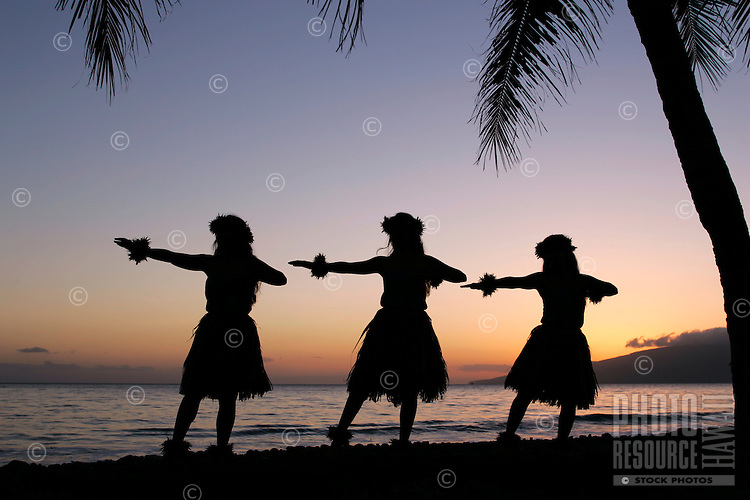 Three hula dancers at sunset in Olowalu, Maui.