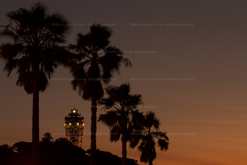 Enoshima Island light house seen behind palm trees at sunset , Kanagawa, Japan. Monday October 23rd 2017