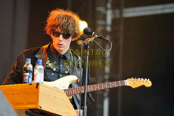 Blaine Harrison of The Mystery Jets.performing on Day 2 at Reading Festival, Reading, England. .25th August 2012.on stage in concert live gig performance performing music half length black fringed jacket sunglasses shades guitar  .CAP/MAR.© Martin Harris/Capital Pictures.