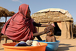 Fatna bathes her son Abdulbasid in a camp for internally displaced persons outside Kubum, in South Darfur, where international agencies are providing water, sanitation and other emergency services.