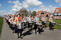 Koningsdag in Marken. Tijdens Koningsdag dragen veel inwoners van Marken klederdracht met oranje accenten. De fanfare loopt door het dorp