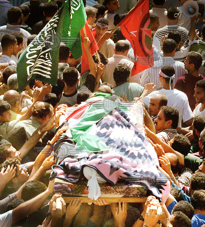 © Ami Vitale / Panos Pictures..Yusuf Khalifa,18, is carried out of a mosque in Gaza Monday, October 9, 2000.
