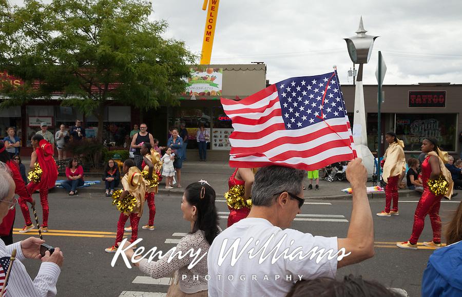 Man waving American Flag, Independence Day Parade 2016, Burien, Washington, USA.