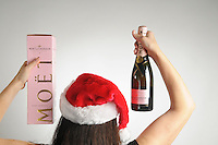 Christmas-woman back , holding bottle of ping champagne