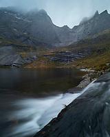 River flows into lake Storvatnet with Stjerntind mountain peak rising above, Flakstadøy, Lofoten Islands, Norway