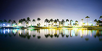 A long-exposure night view includes the reflection of coconut trees, buildings and harbor lights in Rainbow Tower Pond, Hilton Hawaiian Village, O'ahu.