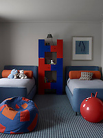 A Tom Dixon bookcase stands between twin beds in the boys' bedroom
