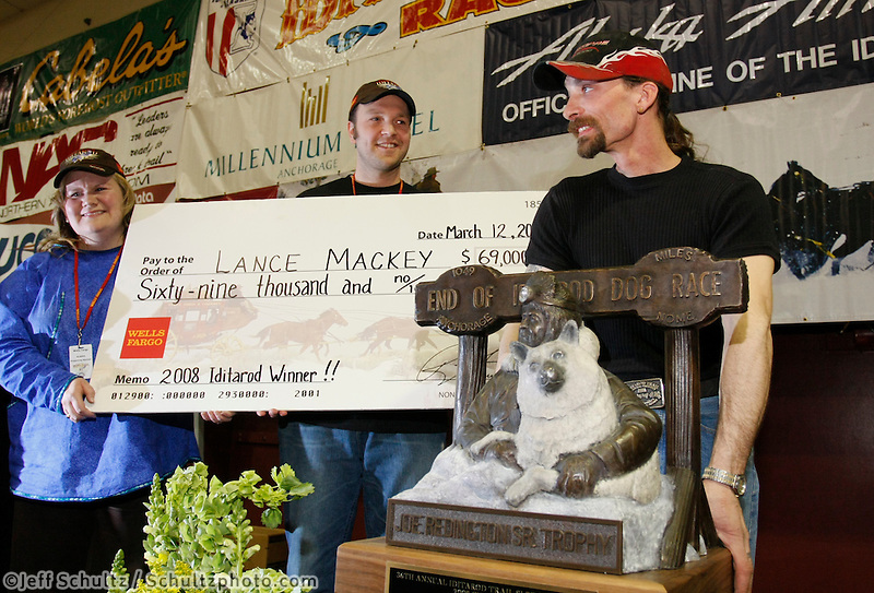"2008 Iditarod Champion Lance Mackey poses with his 1st place ""Joe Redington Sr."" trophy and $69,000 check at the Nome awards banquet on Sunday night"