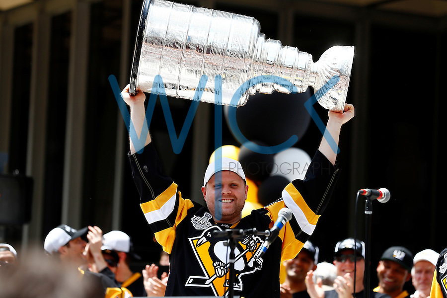 Phil Kessel #81 of the Pittsburgh Penguins hoists the Stanley Cup on stage during the victory parade in downtown Pittsburgh, Pennsylvania on June 15, 2016. (Photo by Jared Wickerham / DKPS)