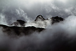 Mountains poke through fog and clouds.