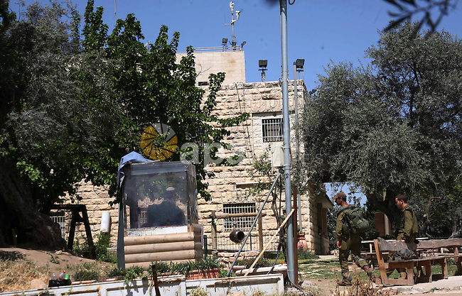 Israeli soldiers stand guard in the garden of a Palestinian house in the southern West Bank city of Hebron from which an Israeli court ordered the Israeli settlers out by May 15 after ruling on April 23, 2012 that their claim to ownership was false. An expert with Israeli settlement watchdog Peace Now said the central Hebron property, known as the Bakri house, was taken over by settlers in 2001 after Zakaria Bakri and his wife were driven out. Photo by Mamoun Wazwaz