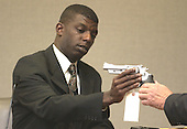 Earl Lee Dancy Jr. of Tacoma, Washington reaches for a pistol as he testifies during the penalty phase of the trial of convicted sniper John Allen Muhammad in courtroom 10 at the Virginia Beach Circuit Court in Virginia Beach, Virginia on November 18, 2003.  John Muhammad was convicted of capital murder on November 17, 2003 for his role as organizer of a two-man sniper team that killed 10 people and terrorized the Washington, D.C. area in 2002. <br /> Credit: Dave Ellis - Pool via CNP