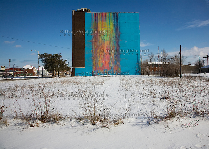 Detroit: paesaggio urbano d'inverno. Un grosso edificio con la facciata coloratissima. Intorno neve e case.
